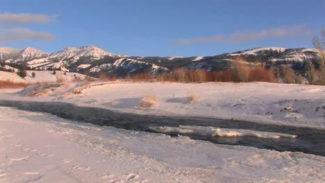 A-cold-river-flows-through-a-snowy-landscape