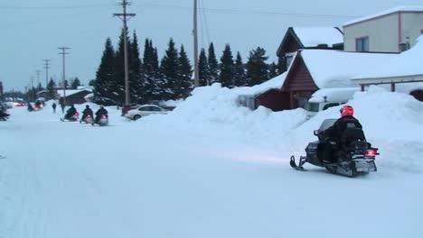 A-snowmobile-rides-his-snowmobile-through-a-town
