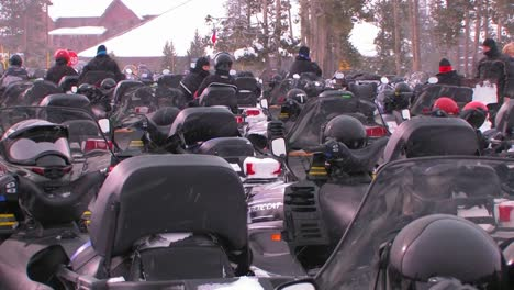 Many-snowmobiles-are-lined-up-in-a-snowmobile-parking-lot-1