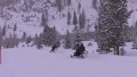 Una-Larga-Fila-De-Motos-De-Nieve-Se-Dirige-A-Través-De-Un-Desierto-Nevado