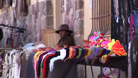 A-latin-American-man-sits-at-a-souvenir-stall-selling-goods-along-a-street-in-South-America