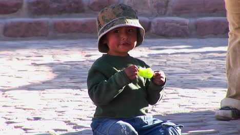 A-Latin-American-boy-sits-on-the-ground-and-eats-a-green-popsicle-in-a-South-American-village
