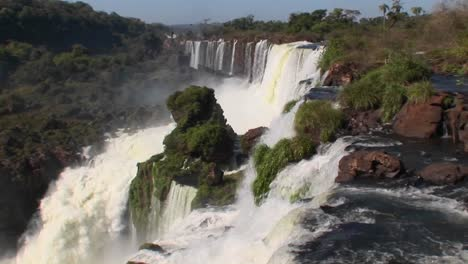 Iguacu-Falls-flows-out-of-the-jungle-with-a-rainbow-foreground-1