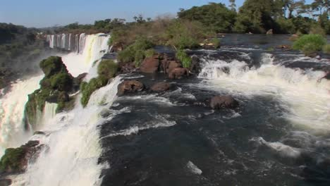 Pan-across-Iguacu-Falls-flowing-out-of-the-jungle-with-a-rainbow-foreground
