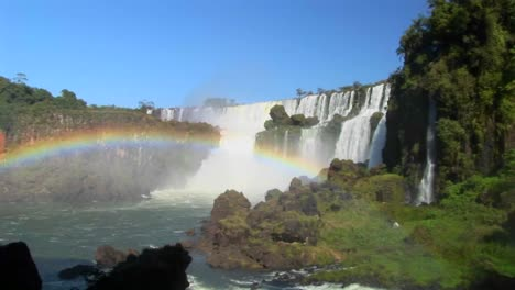 A-beautiful-wide-shot-of-Iguacu-Falls-with-a-rainbow-foreground