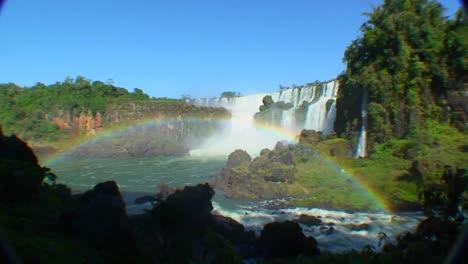 Argentina-Iguazu-Falls-wide-angle-with-rainbow-and-blue-sky-