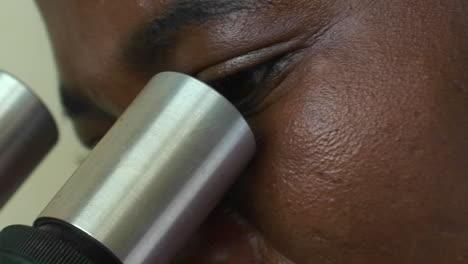 A-technician-examines-a-specimen-through-a-microscope-1