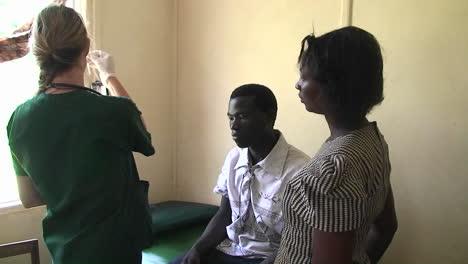A-nurse-in-a-clinic-takes-a-man-s-temperature