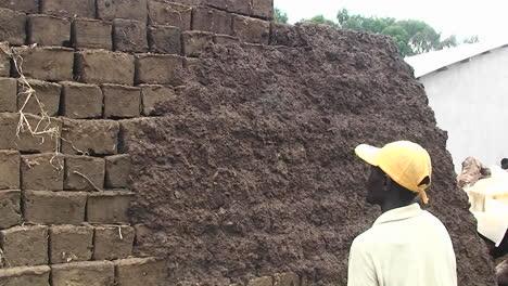 A-man-throws-handfulls-of-daub-on-a-mud-bricked-wall