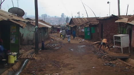 People-walk-down-a-dirty-street-in-a-shanty-town