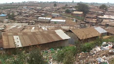 La-Gente-De-Pie-En-Una-Colina-Mira-Hacia-El-área-Circundante-Del-Barrio-De-Chabolas