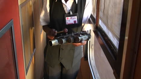 An-attendant-on-a-train-walks-up-and-down-the-aisle-ringing-a-bell