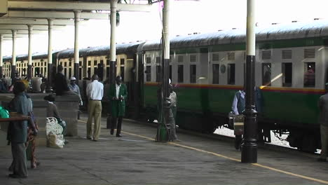 People-walk-along-side-of-a-train-in-a-station