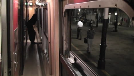 A-person-stands-looking-out-the-window-as-the-train-leaves-the-station-and-a-man-walks-along-on-the-platform