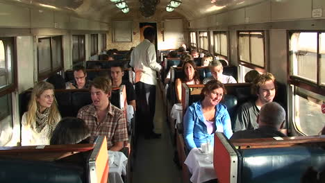 An-attendant-passes-through-a-train-car-carrying-a-plate-as-passengers-talk-and-look-out-the-window
