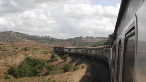 A-train-travels-a-rural-area-past-a-small-village