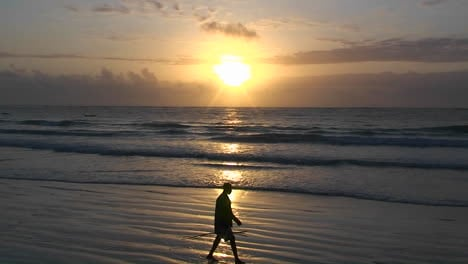 A-man-walks-along-the-beach-carrying-a-stick-as-the-waves-come-in-and-the-sun-sets