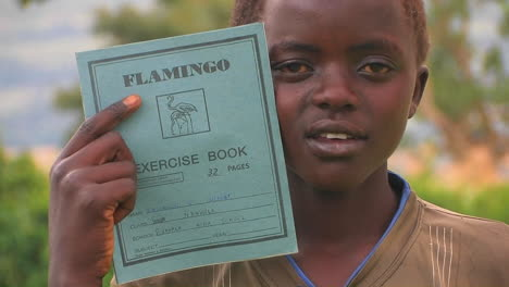A-young-boy-holds-up-his-notebook-pointing-to-the-wording-and-picture