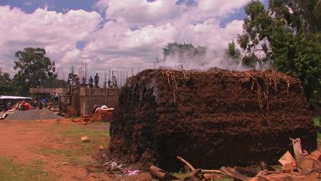 Los-Hombres-Están-Construyendo-Un-Edificio-Y-Sale-Vapor-De-Una-Gran-Pila-De-Tierra-