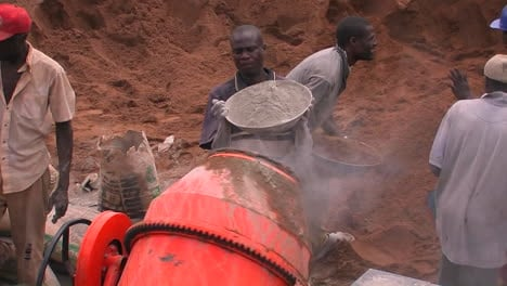 Men-throw-cement-and-aggregate-into-a-cement-mixer