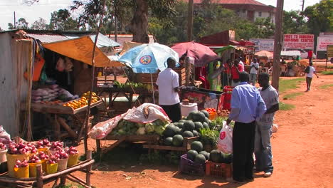 People-buy-produce-at-stands-cars-pass-by-on-the-street