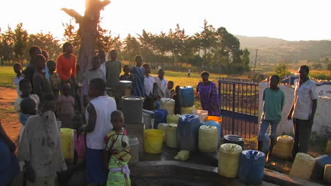 People-filling-up-canisters-with-water-from-a-water-pump