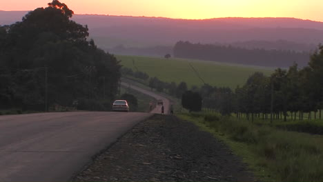 Vehicles-travel-a-rural-highway-near-sunset