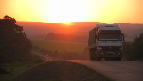 A-truck-travels-down-a-rural-highway-near-sunset