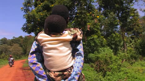 A-mother-carries-a-child-on-a-rural-dirt-road