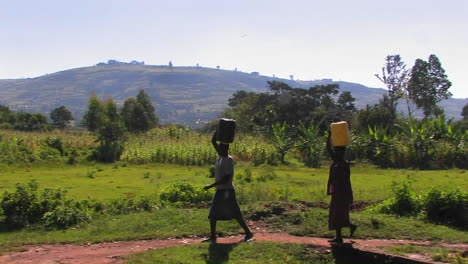 Women-walk-along-a-path-in-a-rural-area-carrying-packages-on-their-heads