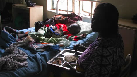 A-woman-sits-next-to-the-bed-of-a-child-in-a-hospital-and-eats-food-from-a-tray