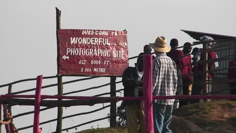 People-stand-at-a-photographic-site-and-a-vendor-attempts-to-sell-something-to-a-man