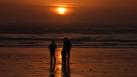 Una-Familia-Se-Encuentra-En-La-Playa-Recortada-Contra-El-Sol-Poniente