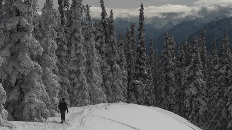 A-man-snowshoes-across-a-snowy-mountainside