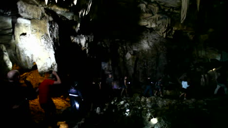 People-explore-a-dark-cave-with-flashlights