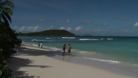 La-Gente-Pasea-Por-La-Playa-De-Una-Isla-En-El-Caribe