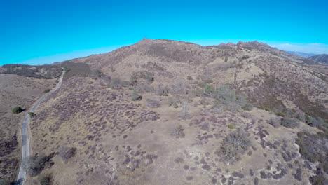 Eine-Aufsteigende-Antenne-über-Einer-Kargen-Berglandschaft-Und-Ein-Auto-Das-Eine-Einsame-Straße-Befährt