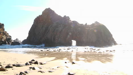Waves-roll-into-shore-on-a-sunny-day-along-California-coastline-with-an-arch-rock-foreground