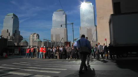 Construction-workers-and-pedestrians-pass-along-a-crosswalk-on-a-busy-urban-street-