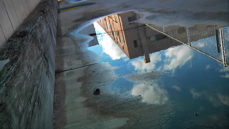 Time-lapse-of-clouds-passing-over-an-urban-building-as-reflected-in-a-puddle-on-the-pavement-