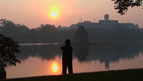 A-woman-practices-tai-chi-in-front-of-a-lake-in-Hanoi-Vietnam