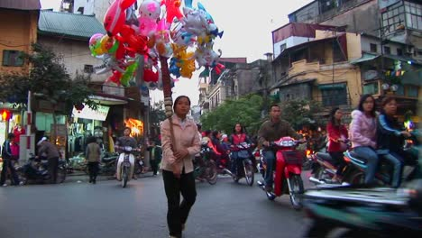 A-woman-walks-with-balloons-through-a-busy-street-in-Hanoi-Vietnam