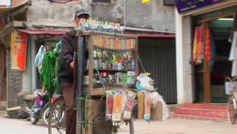 Un-Hombre-Pedalea-Una-Bicicleta-Cargada-Con-Medicamentos-Y-Otros-Bienes-Por-Una-Calle-Estrecha-En-Vietnam