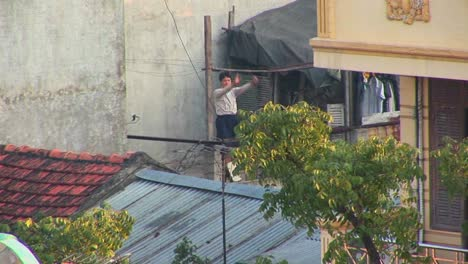 A-man-exercises-on-his-rooftop-in-the-early-morning-in-Vietnam