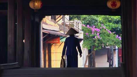 A-woman-walks-under-a-bridge-in-a-small-village-in-Vietnam