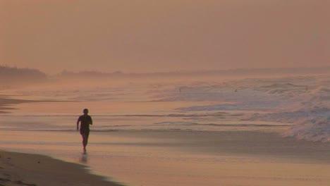 A-man-jogs-along-a-beach-in-silhouette