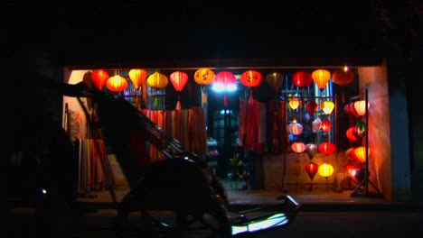 Bicicletas-Y-Rickshaws-Pasan-Por-Una-Colorida-Tienda-De-Linternas-Por-La-Noche-En-Vietnam