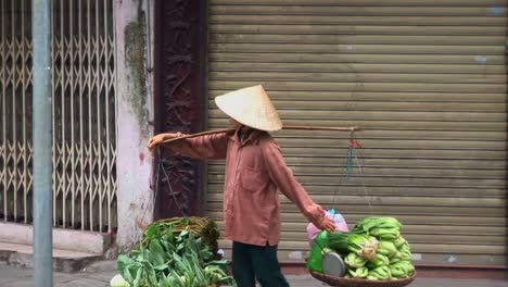 A-woman-carries-a-heavy-load-along-the-street-in-Vietnam