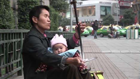 A-blind-man-plays-music-along-a-street-in-modern-China