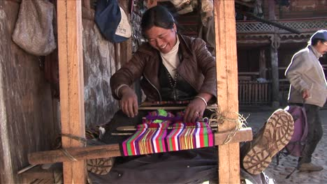 A-woman-operates-a-basic-loom-in-a-Chinese-village